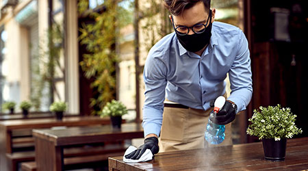 man sanitizing a table